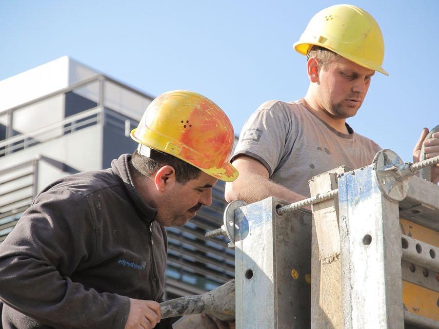 2 bouwvakkers van de B&R Bouwgroep die beton aan het storten zijn.